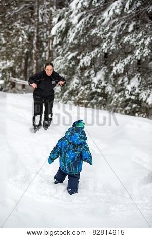 Mother Playing With Son Outside In The Snow