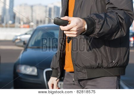Male holding car keys with car on background