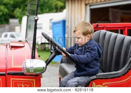 Boy Pretending To Drive An Old Fire Truck