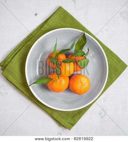 Tangerines On White Wooden Background And Green Fabric