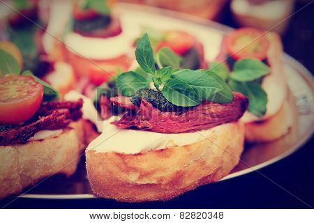 Bruschettas with beefsteak and pesto sauce, close-up, toned image