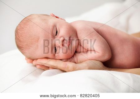 newborn baby lying down on mother's hands face closeup body care maternity caucasian white