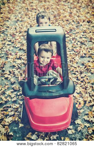 Boys Playing In A Toy Car Outside - Vintage Filtered