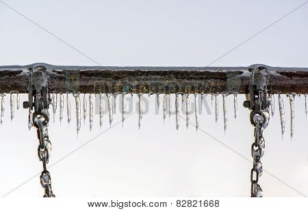 Close Up Of Ice Covered Swing Bar And Chains