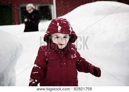 Happy Boy In A Red Jacket On A Snowy Day