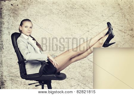 Businesswoman in office chair with her feet up on anything