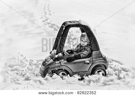 Young Boy In A Toy Car Stuck In The Snow - Black And White