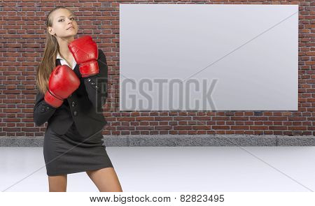 Businesswoman posing in boxing gloves. Brick wall with blank banner as backdrop