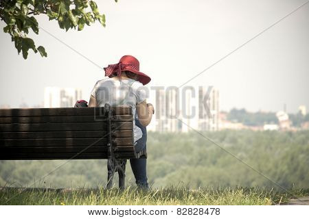 woman with red hat sitting on a bench of Kalemegdan Fortress of Belgrade