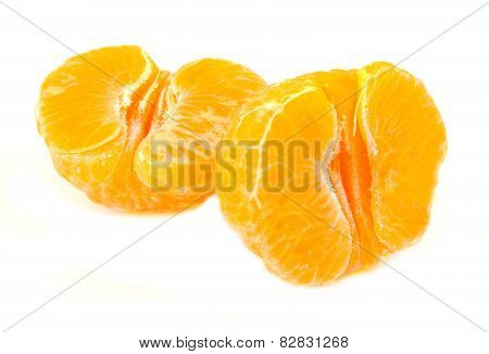 Closeup view of two unpeeled tangerine halves, orange fruit, citrus on white background