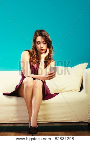 Woman Sitting On Couch Using Mobile Phone.