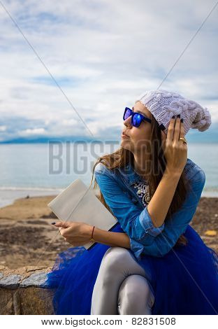 Pretty young girl in blue pettiskirt  with book