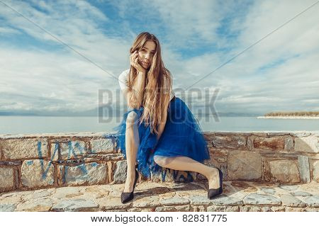 Pretty young girl in blue pettiskirt  seating on stones