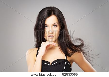 Portrait of the young, beautiful and cute girl with a blowing brunette hair.