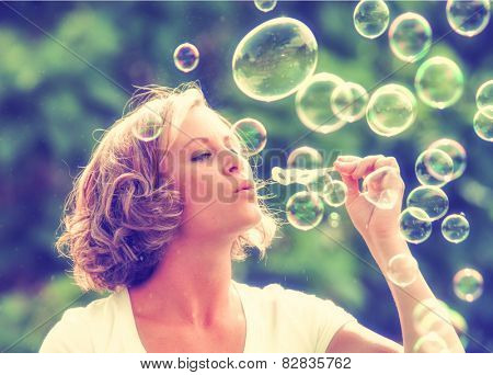a beautiful woman blowing bubbles toned with a retro vintage instagram filter effect app or action