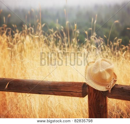 a hat on a fence during sunset or sunrise toned with an instagram like filter