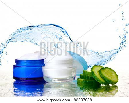 Cream and fresh sliced cucumber on mirror surface on abstract water splashing background