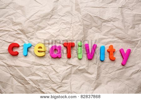 Creativity motto by alphabet letters on crumpled paper background