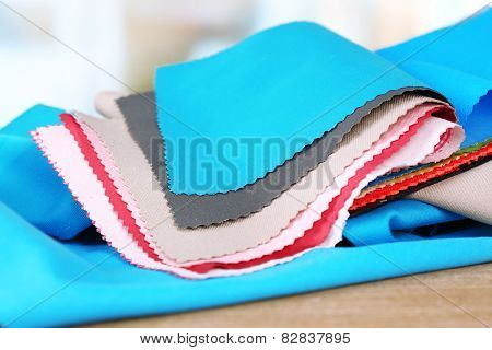 Colorful fabric samples on wooden table and light blurred background