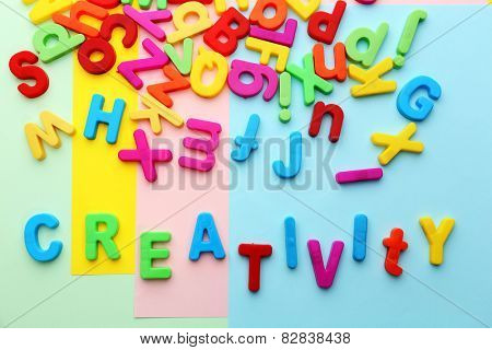 Creativity motto by alphabet letters on colorful sheets of paper background