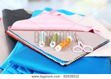 Colorful fabric samples. threads and scissors on table and light blurred background