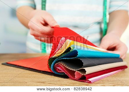 Colorful fabric samples in female hands on light blurred background
