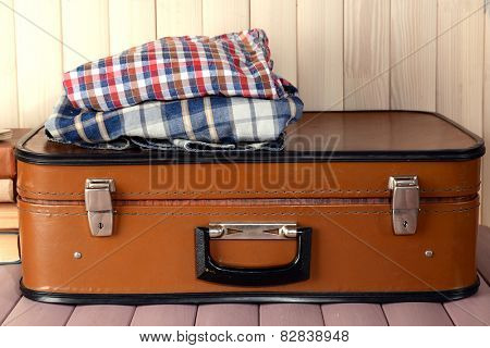 Vintage suitcase with clothes on wooden background
