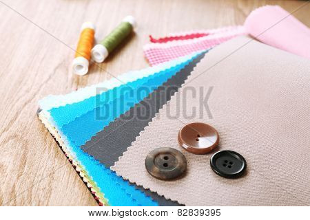 Colorful fabric samples with buttons and threads on wooden table background