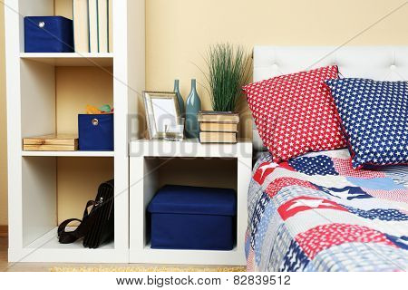 Modern colorful bedroom interior with bed and nightstand, with design details on light wall background