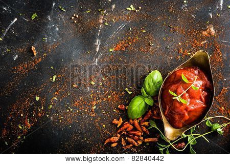 tomato sauce in a gravy boat and spices on textured black background