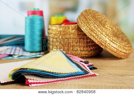 Colorful fabric samples and wicker basket of threads on wooden table and light blurred background