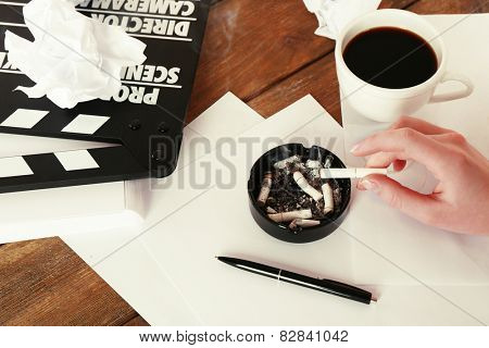 Female hand with cigarette, moving clapper and sheets of paper on wooden background