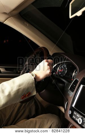 Man driving his modern car at night in city, close-up