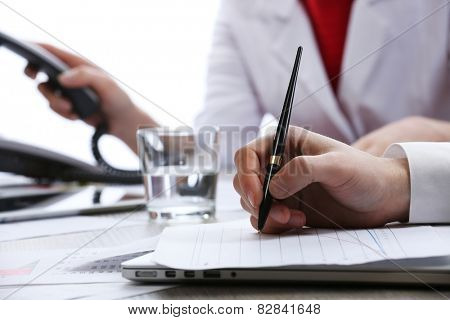 Signing of documents at worktable on white blurred background