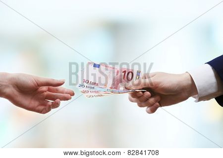 Businessman giving money on light blurred background