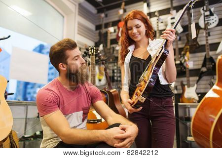 music, sale, people, musical instruments and entertainment concept - happy couple of musicians with guitar at music store