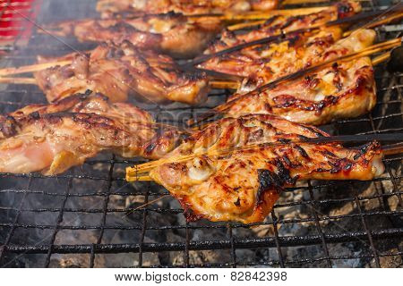 Grilling chicken on charcoal grill
