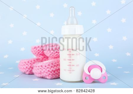 Baby milk bottle, pacifier and babys bootees on blue background