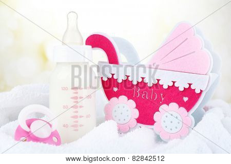 Baby milk bottle and pacifier on towel on bright background