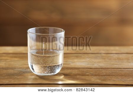 Glass of clean mineral water on rustic wooden background