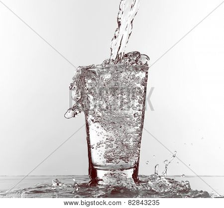 Water pouring in glass isolated on white