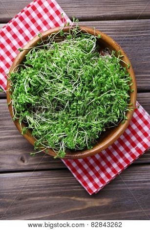 Fresh cress salad in bowl on napkin and wooden planks background