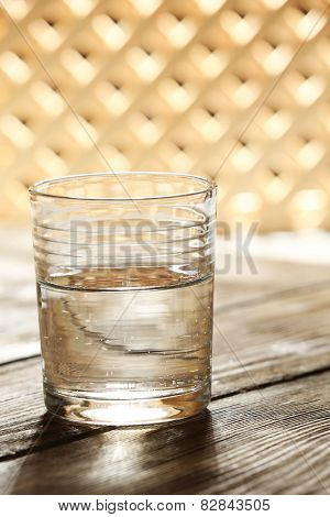 Glass of clean mineral water on wooden surface and lattice background