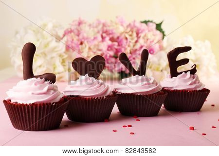 Delicious Valentine Day cupcakes on light background