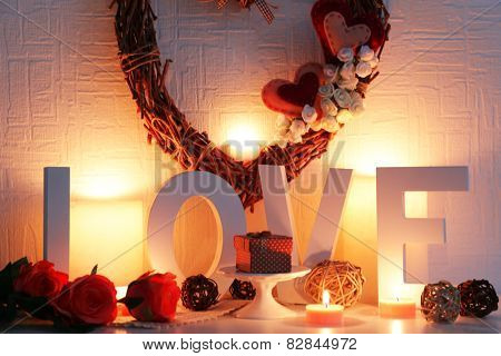 Romantic still life with wicker heart, word LOVE and candle lights on mantelpiece and white wall background