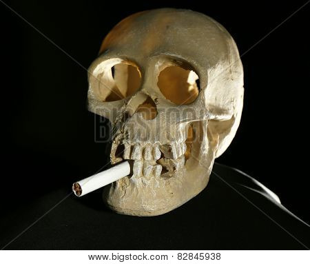 Human scull and wooden hand with cigarette on dark background