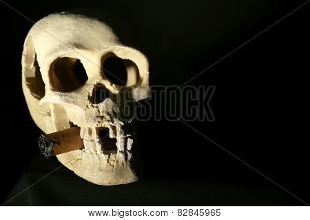 Smoking human scull with cigar in his mouth on dark background