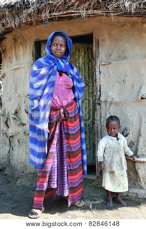 Maasai Woman With Child Standing At Door Of Her Hut.