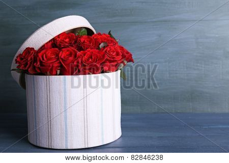 Bouquet of red roses in textile box on wooden background
