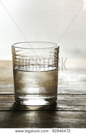 Glass of clean mineral water on surface and background
